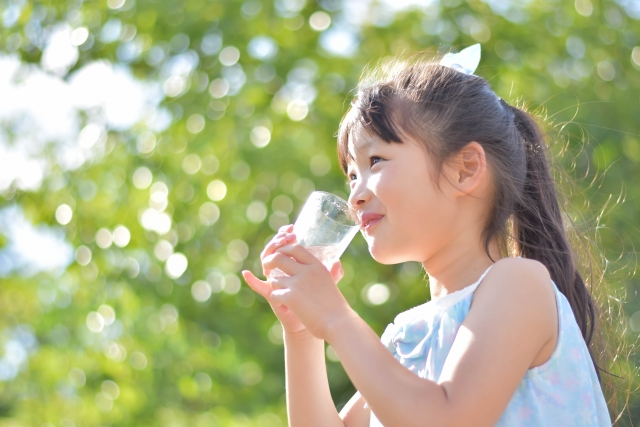 コップで水を飲む女の子