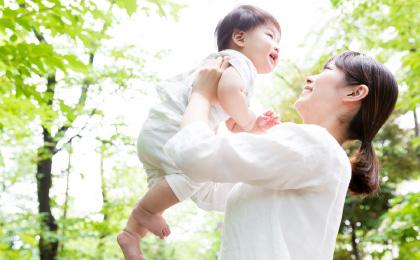 お母さんに高い高いされて微笑む赤ちゃん